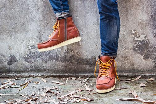 Un homme portant des bottes à lacets avec une jean.