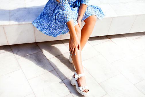 Une femme avec des belles sandaleset une robe bleue.