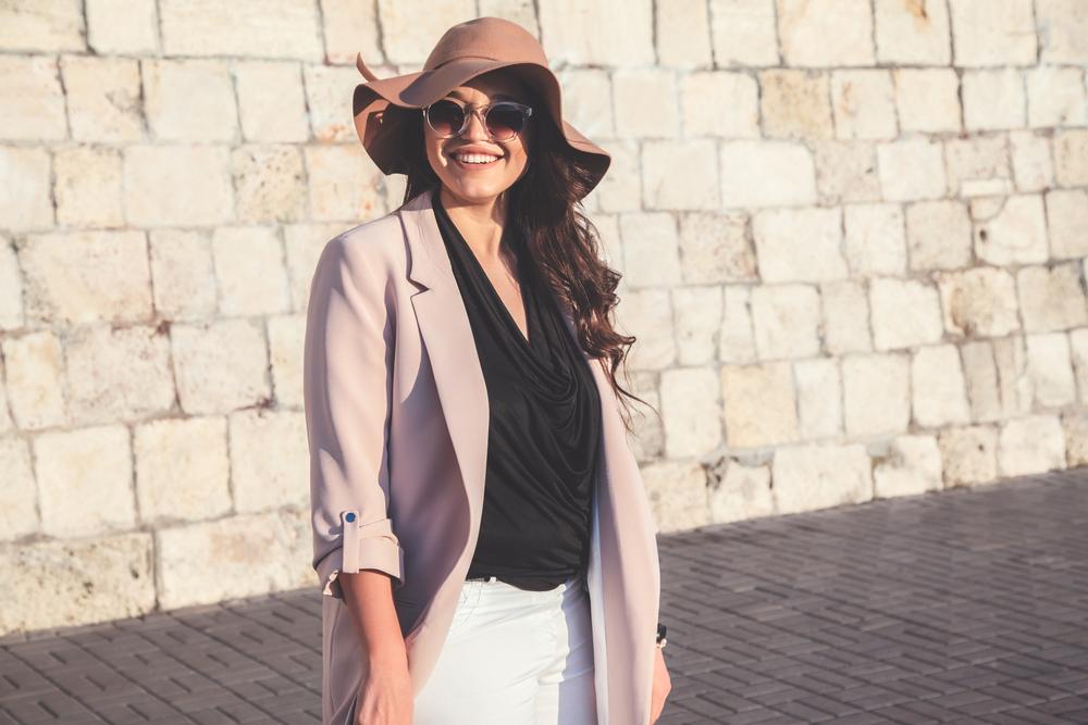 Femme portant un blazer beige surdimensionné, un chapeau beige et une blouse noire.